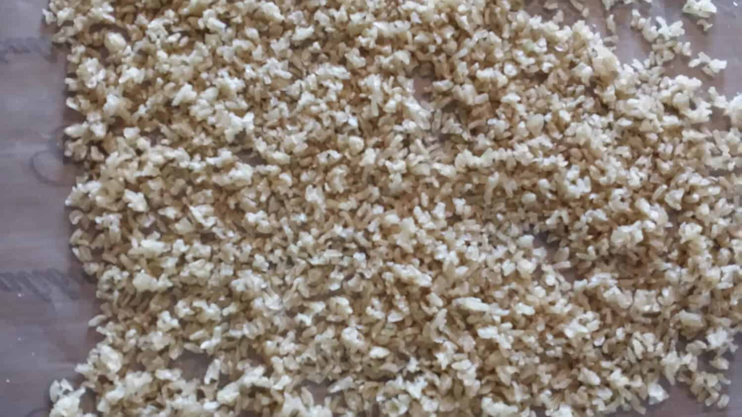 partially dehydrated unclumped rice on dehydrator tray