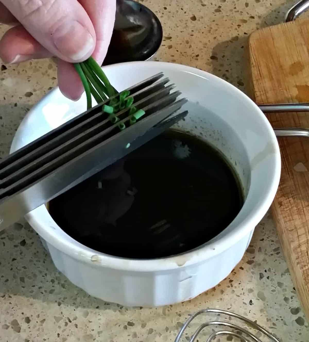 snipping chives with herb scissors for Balsamic vinaigrette