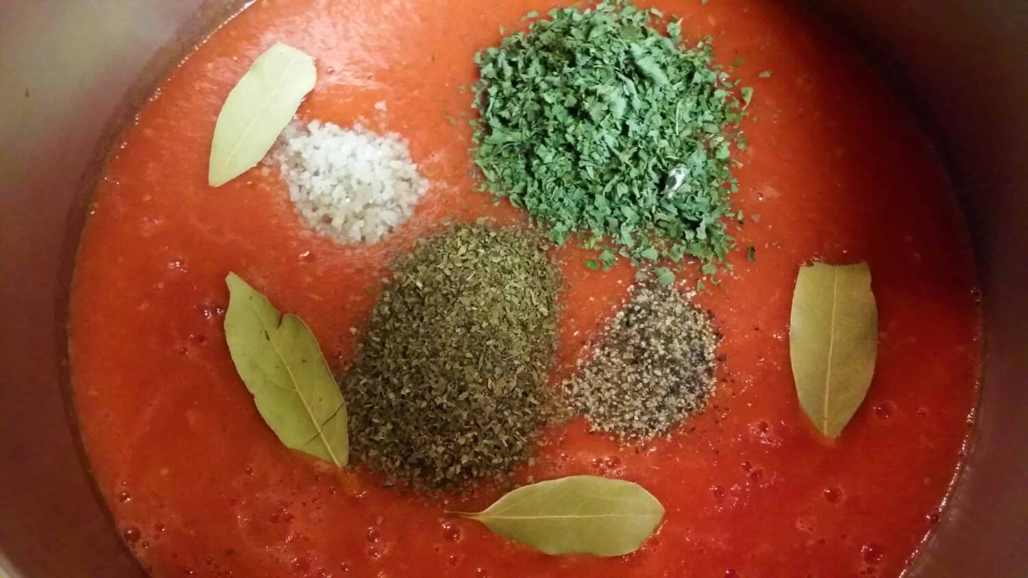 Adding the herbs and seasonings to the homemade pizza sauce