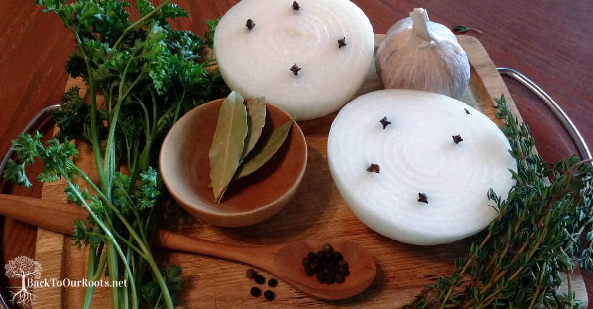 onions, peppercorns, garlic and bay leaves on wooden cutting board