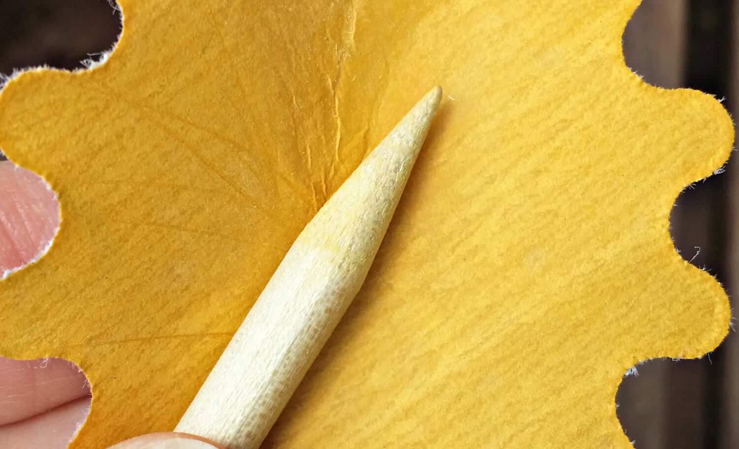 pointed end of wooden dowel sanded smooth for DIY drop spindle