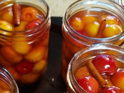 pint jars with cherries in apple cider