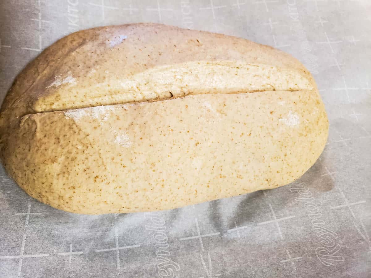 Bucket Dough Bread loaf with slash on parchment paper