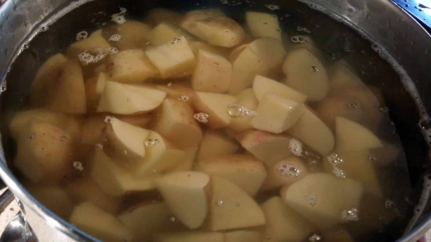 roughly chopped potatoes in a pan of salt water