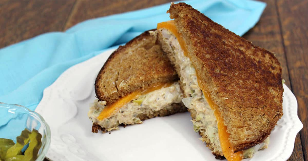 tuna melt sandwich on white plate with blue napkin