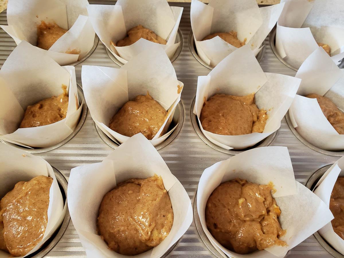 Sourdough Cinnamon Pecan Muffin batter in cupcake papers in muffin tin