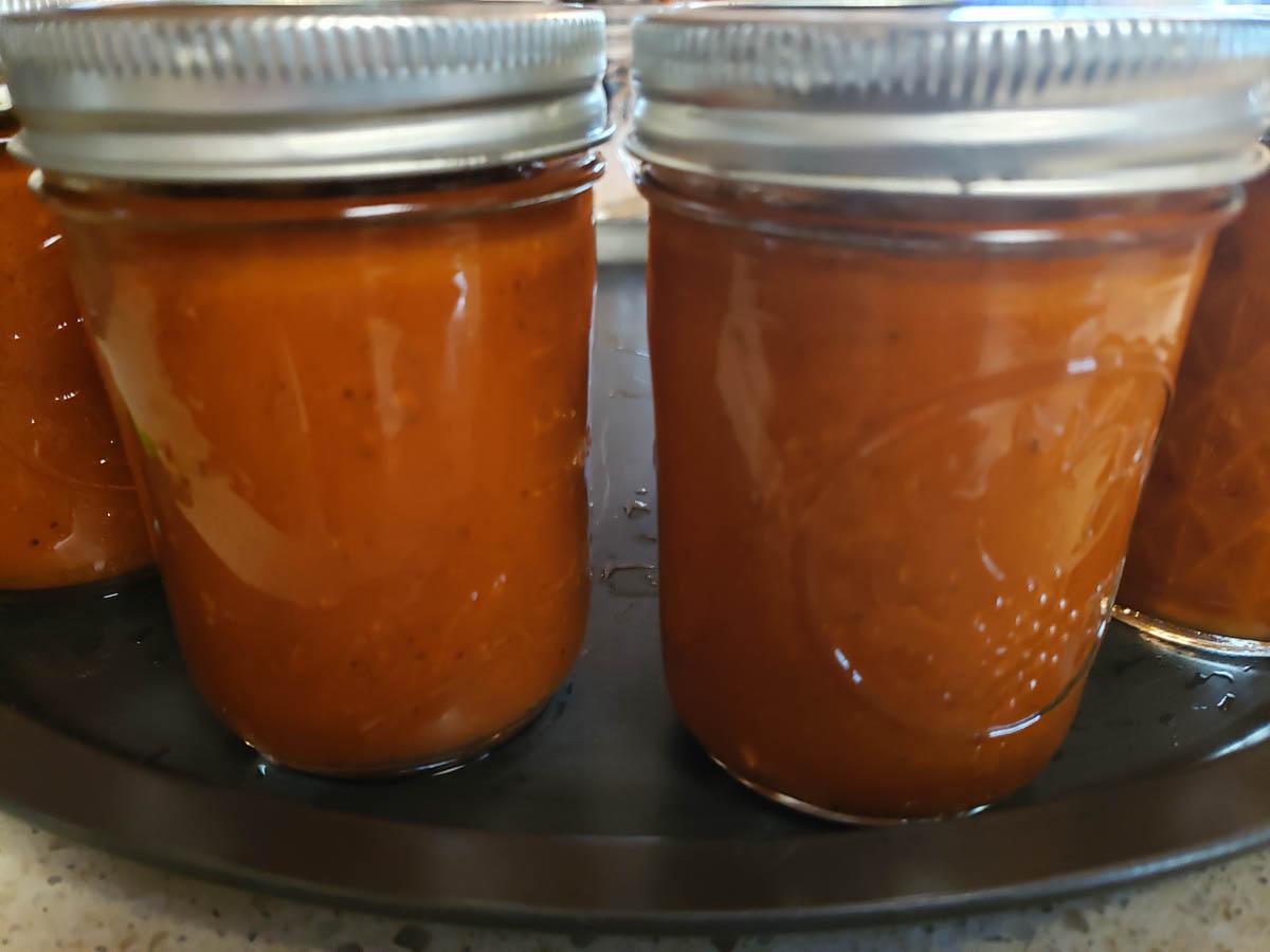 canned Marinara Sauce in half pint jars on pizza pan